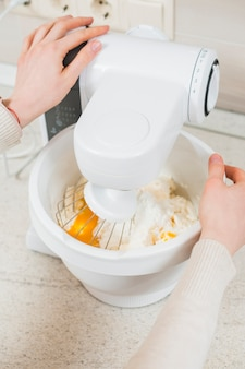 Ritaglia le mani mescolando la pastella per la pasticceria
