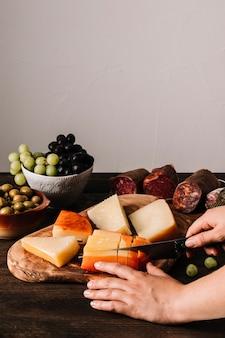 Ritaglia le mani tagliando il formaggio a pasta molle