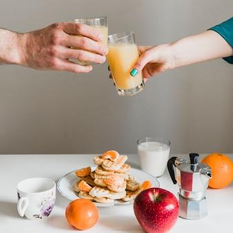Ritaglia le mani tintinnio di bicchieri con succo