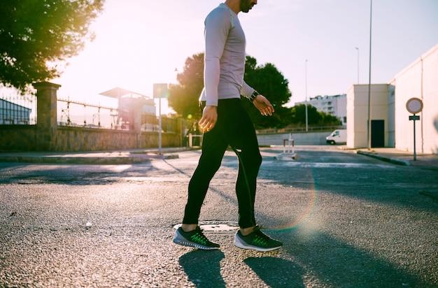 Ritaglia lo sportivo camminando sulla strada