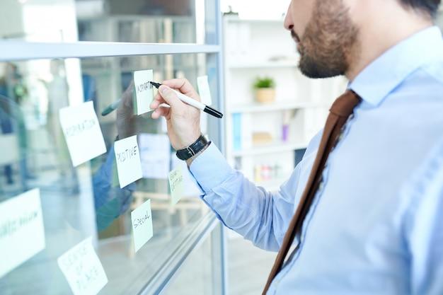 Ritaglia uomo organizzando note adesive