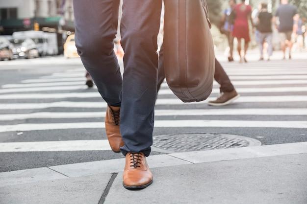 Ritagliare le gambe facendo un passo sul marciapiede