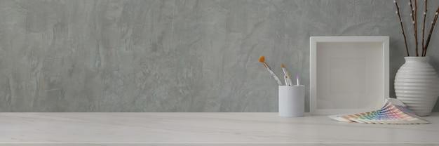Ritagliata area di lavoro alla moda con forniture di design e decorazioni sulla scrivania in marmo