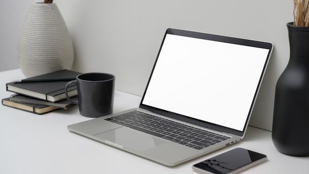Ritagliata area di lavoro con laptop schermo vuoto, smartphone, forniture per ufficio e decorazioni