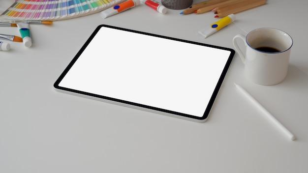 Ritagliata area di lavoro di design con tablet schermo vuoto, tazza di caffè e forniture di design
