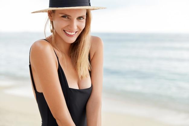 Ritagliata colpo di bella giovane donna positiva ricreare sulla spiaggia esotica durante la calda estate wher, vestito in costume da bagno e cappello di paglia, posa contro il meraviglioso oceano con onde tranquille. concetto di svago