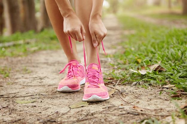 Ritagliata colpo di corridore di giovane donna che stringe i lacci delle scarpe da corsa, preparandosi per fare jogging all'aperto.