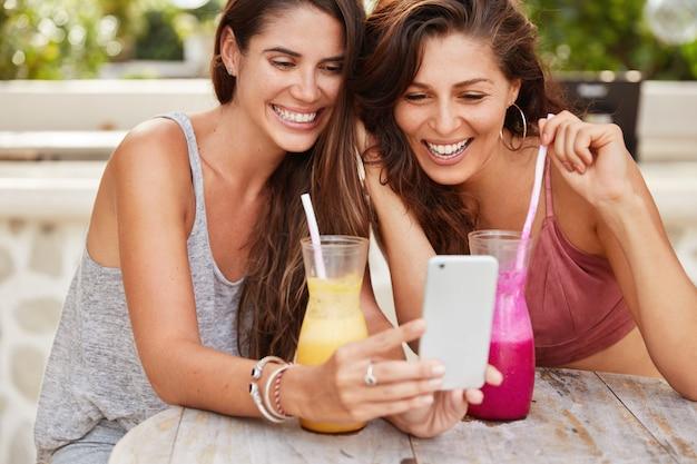 Ritagliata colpo di felici giovani donne felici fanno shopping nei negozi web, felici di scegliere un nuovo acquisto