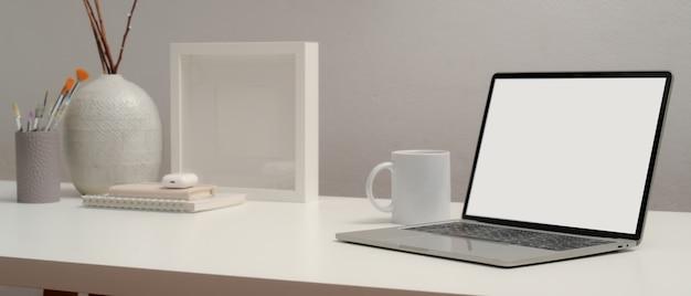 Ritagliata colpo di laptop con schermo vuoto sul tavolo con cancelleria e decorazioni nella stanza del ministero degli interni