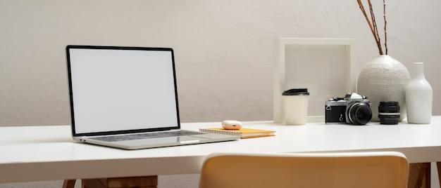 Ritagliata colpo di laptop con tracciato di ritaglio sul tavolo bianco con cancelleria, macchina fotografica e decorazioni in ufficio a casa