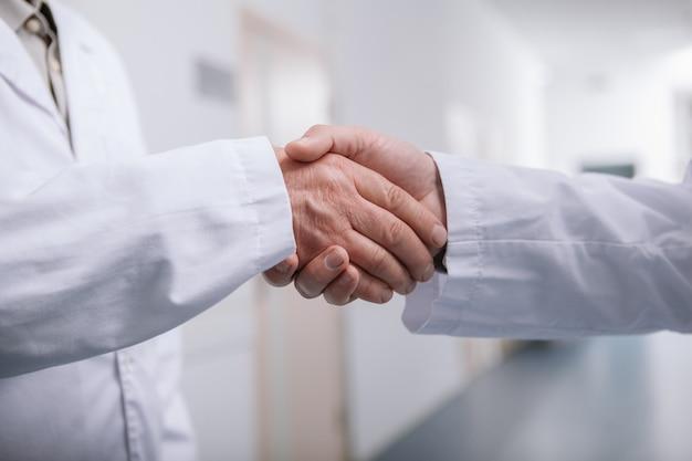 Ritagliata da vicino di due medici maschi che stringono la mano