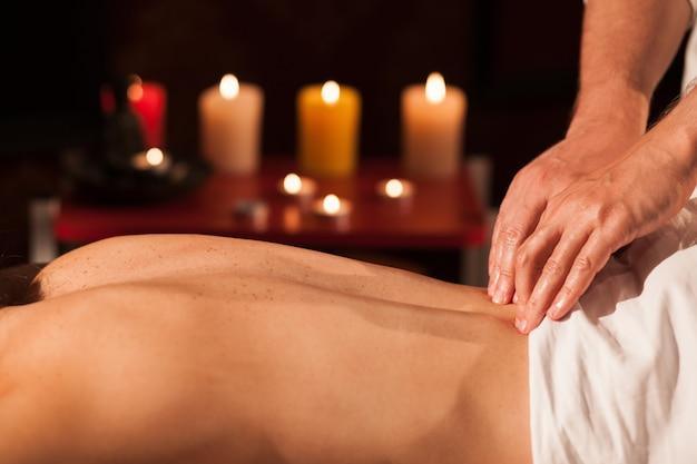 Ritagliata da vicino le mani di un abile massaggiatore che lavora con il suo cliente. massaggiatore professionista che massaggia indietro di una donna alla stazione termale, candele che bruciano sui precedenti, spazio della copia. tempo libero, benessere
