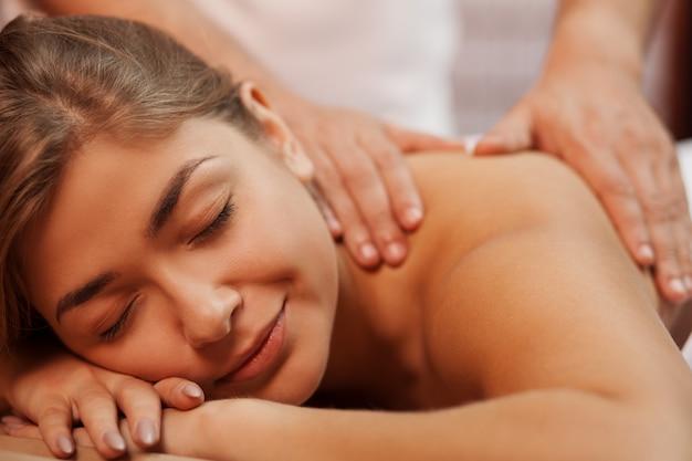Ritagliata da vicino su una bellissima giovane donna in buona salute felice che sorride con gli occhi chiusi, mentre massaggiatore professionista massaggiandola schiena e spalle, copia spazio. cure mediche, alleviare lo stress