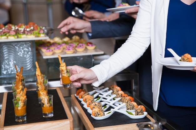 Ritagliata donna prendendo snack dalla tabella a buffet