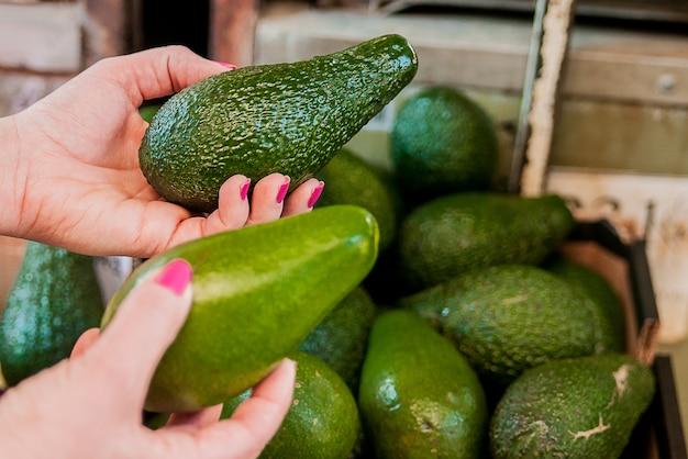 Ritagliata immagine di un cliente che sceglie avocado nel supermercato. vicino di donna mano che tiene avocado nel mercato. vendita, shopping, cibo, consumismo e concetto di persone