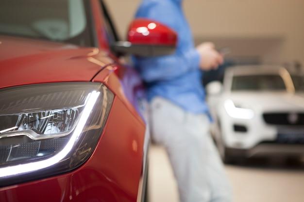 Ritagliata immagine ravvicinata di luci per auto, uomo irriconoscibile che si appoggia sulla macchina su sfondo sfocato