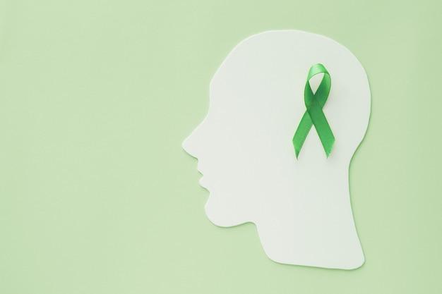 Ritaglio di carta del cervello con il nastro verde su fondo verde, concetto di salute mentale, giornata mondiale della salute mentale