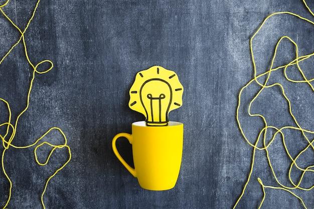 Ritaglio di carta della lampadina gialla nella tazza con la corda della lana sulla lavagna