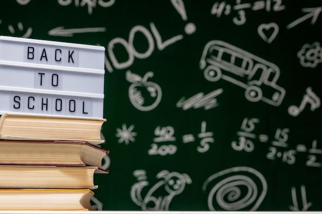 Ritorno a scuola: con libri, matite e globo sul tavolo bianco su una lavagna verde