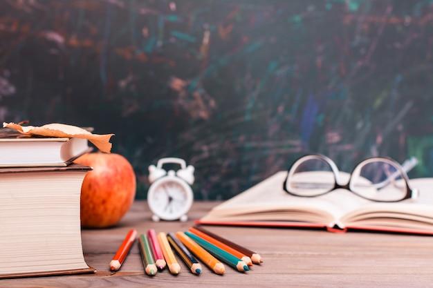 Ritorno a scuola con libri, matite, orologio, libro aperto e bicchieri su un tavolo di legno sopra la lavagna