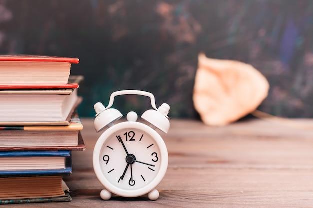 Ritorno a scuola con libri, orologio e foglia caduta