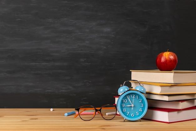 Ritorno a scuola con libri, sveglia, occhiali e mela sulla lavagna.