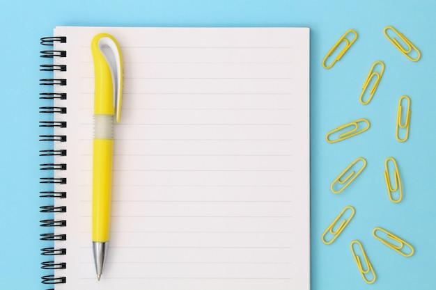 Ritorno a scuola creativo. blocco note con penna gialla e clip su sfondo blu.