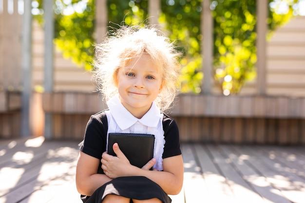 Ritorno a scuola e tempo felice carino bambino industrioso seduto all'aperto. ragazza che legge il libro.