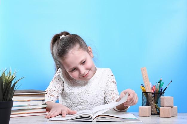 Ritorno a scuola. felice carino bambino laborioso è seduto a una scrivania in casa. il bambino sta imparando in classe.