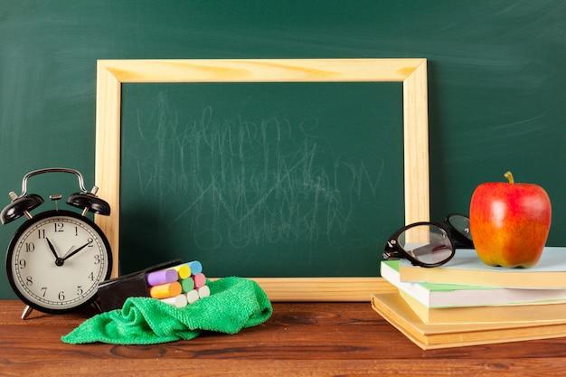 Ritorno a scuola - mela e libri con matite e lavagna