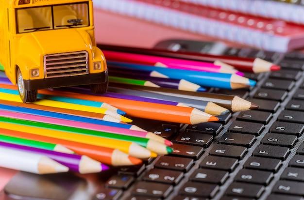 Ritorno a scuola, scuolabus su matite colorate e tastiera