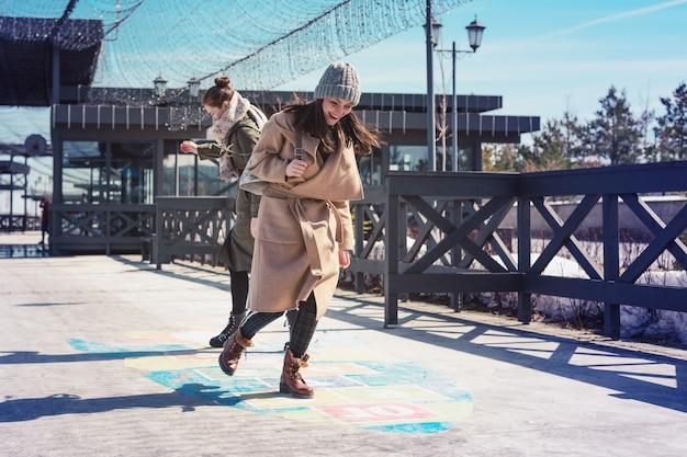Ritorno all'infanzia. due donne che saltano sul marciapiede giocando a campana