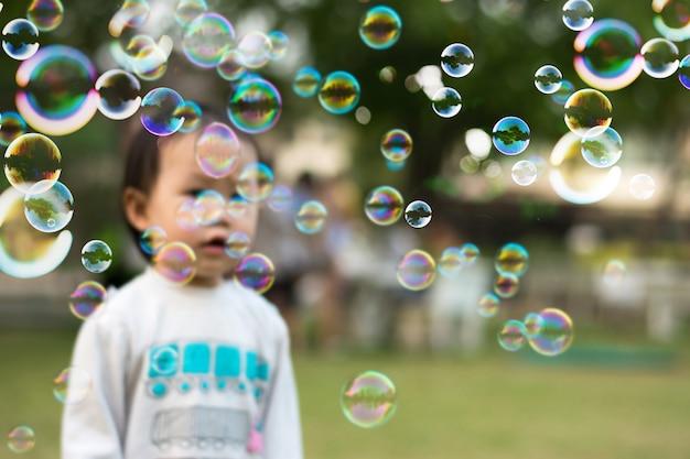 Ritratti di bambina felice che giocano all'aperto nel parco estivo