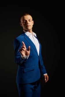 Ritratto a contrasto di un uomo d'affari in un vestito costoso su oscurità