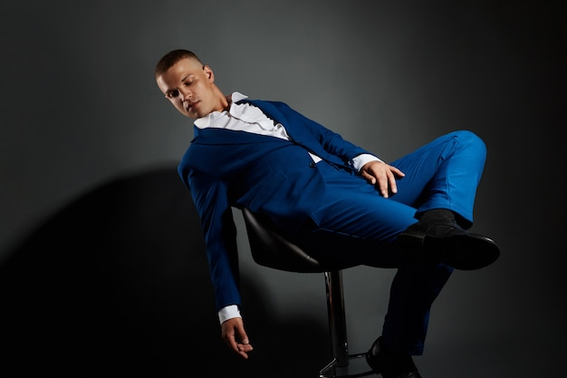 Ritratto a contrasto di un uomo d'affari in un vestito costoso su uno sfondo scuro. riuscito uomo d'affari emozionale del responsabile che posa i gesti con le sue mani sul nero