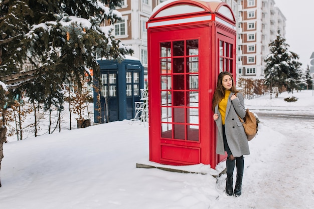 Ritratto a figura intera di bella signora europea con borsa in pelle in piedi vicino alla cabina telefonica e distogliere lo sguardo. foto all'aperto di una splendida donna bianca in cappotto grigio in posa accanto alla cabina telefonica nella giornata invernale.