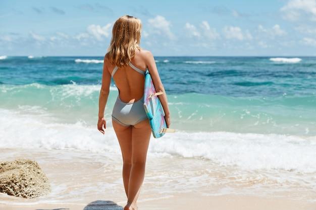 Ritratto a figura intera di donna magra con capelli chiari, indossa un costume da bagno blu, si erge contro la splendida vista dell'oceano con le onde, utilizza la tavola da surf per attività sportive attive, ricrea durante il clima estivo