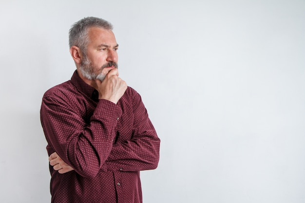 Ritratto a mezzo busto di un uomo barbuto serio dai capelli grigi in una camicia bordeaux su bianco