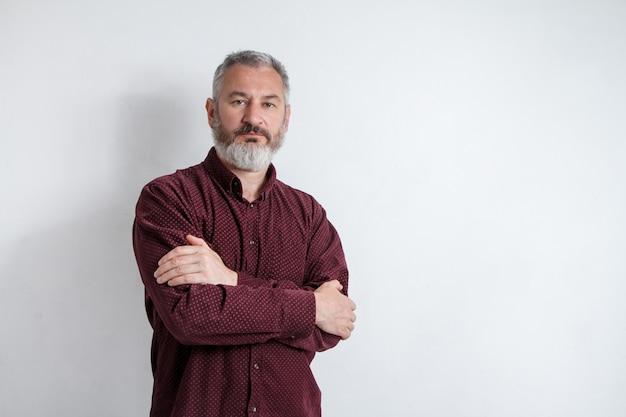 Ritratto a mezzo busto di un uomo barbuto serio dai capelli grigi in una camicia bordeaux su sfondo bianco