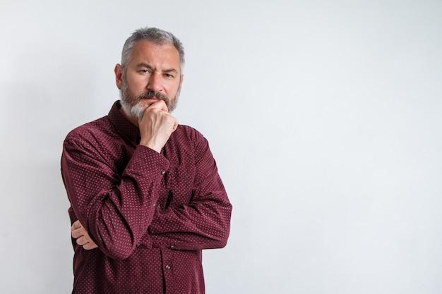 Ritratto a mezzo busto di un uomo barbuto serio dai capelli grigi in una camicia bordeaux