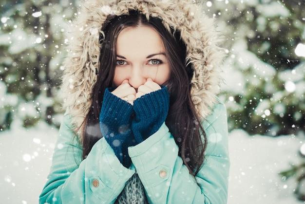 Ritratto all'aperto del primo piano di inverno di giovane castana felice. donna in cappotto invernale al sole