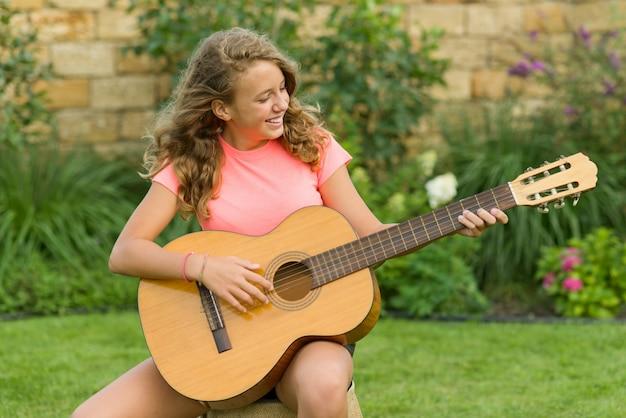Ritratto all'aperto dell'adolescente con la chitarra,