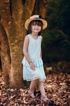 Ritratto all'aperto della bambina adorabile agghindata in vestito bianco.
