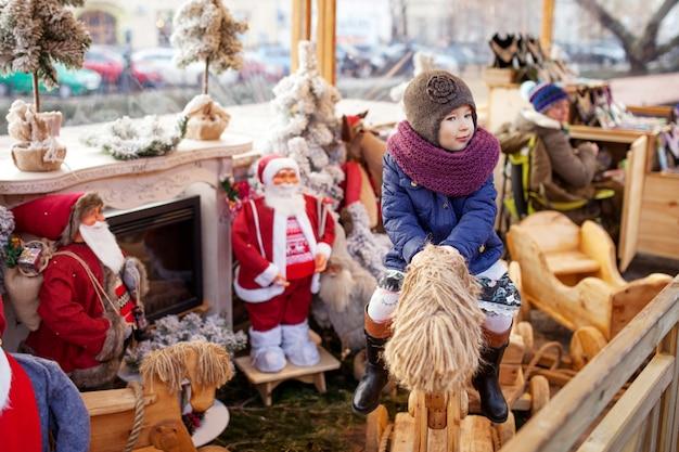 Ritratto all'aperto della bambina sorridente nelle decorazioni di natale sulla via della città europea. concetto di vacanze invernali e natalizie.