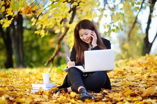 Ritratto all'aperto della bella ragazza asiatica dello studente. giovane donna che studia / che lavora e che gode di bello giorno soleggiato di autunno