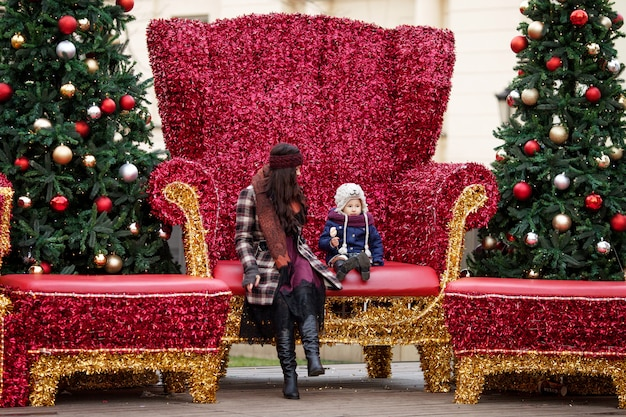 Ritratto all'aperto della donna e della bambina sorridenti in decorazioni di natale sulla via della città. famiglia felice con bambino piccolo. concetto di vacanze invernali e natalizie.