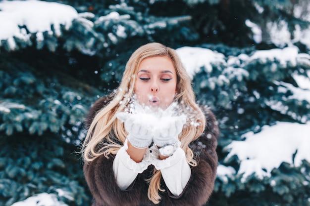 Ritratto all'aperto della ragazza di natale, neve di salto della bella donna nella foresta di inverno