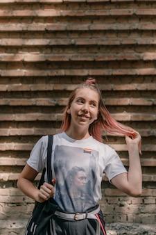 Ritratto all'aperto della ragazza giovane hipster hipster con capelli rosa e segno lgbt