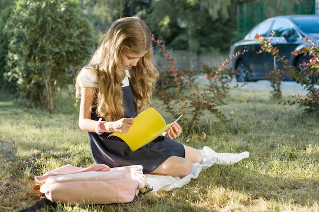 Ritratto all'aperto della scolara che si siede sull'erba