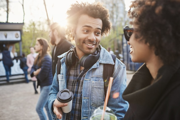 Ritratto all'aperto di amici africa-americani che camminano nel parco mentre parlano e bevono caffè, indossando abiti alla moda.